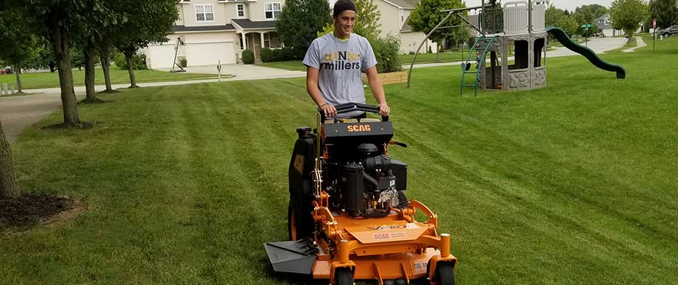 Team member mowing the large front yard of a Noblesville, IN home.